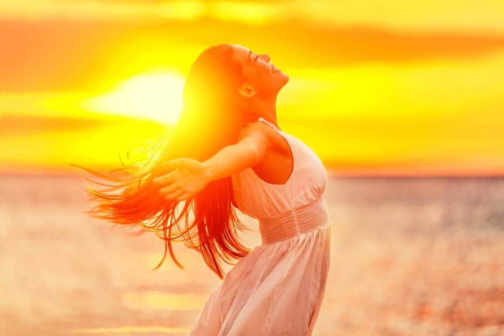 Happy woman feeling free with open arms in sunshine at beach sun